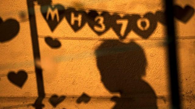 Der Schatten einer Girlande auf einer Wand.