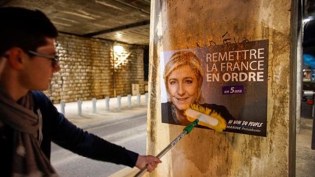 Wahlplakat von Marine Le Pen wird an einer Mauer angebracht.