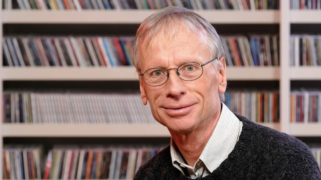 Mann mit Brille vor einem CD-Regal