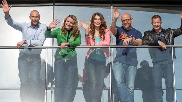 Drei Moderatoren und zwei Moderatorinnen winken an der Reling an Deck der MS Sonnenkönigin.