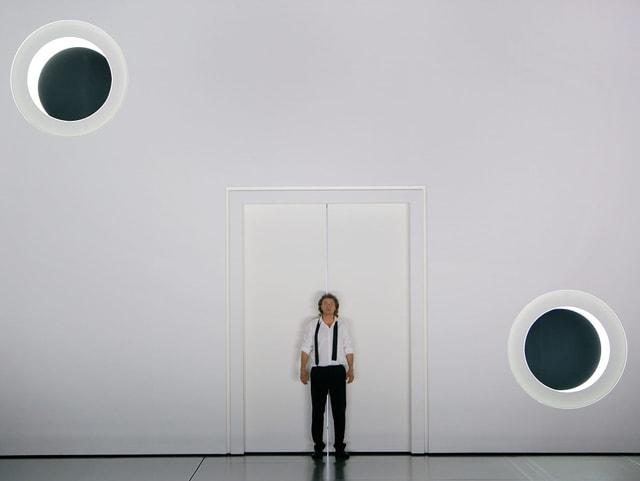 Ein Mann vor einer weissen Tür und einer weissen Wand.