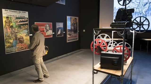 Ein Mann steht vor einem Filmplakat. Er steht in einem Ausstellungsraum.