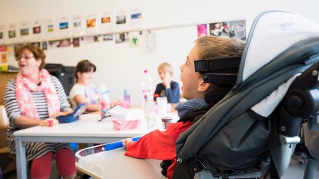 Kleines behindertes Kind im Rollstuhl in einem Schulzimmer mit anderen Behinderten