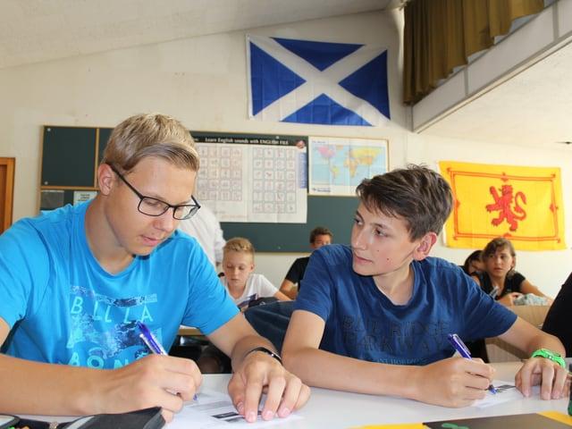 Zwei Schüler sitzen am Pult und diskutieren.