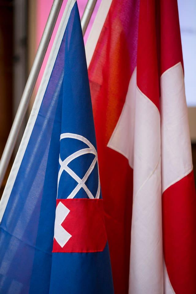 Schweizer Flagge, daneben eine blaue Fahne mit Weltkugel und kleinem Schweizer Kreuz.