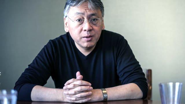 Ein Porträt von Kazuo Ishiguro. Er sitzt am Tisch.