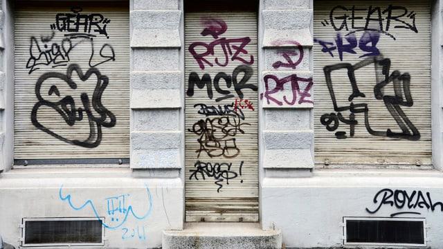 Zu sehen ist eine Zürcher Fassade, welche mit mehreren Schriftzeichen in schwarzer Farbe übersprayt ist.