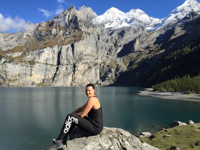 Celine sitzt in Sportleggings und Sportshirt am See