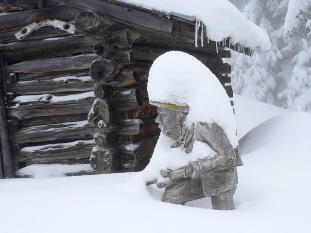 Ein holzgeschnitzter Jäger schaut nur noch knapp aus dem Neuschnee.