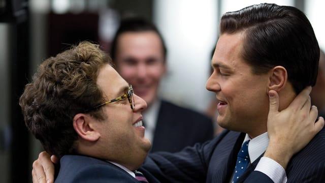 Jonah Hill als Donnie Azoff, Leonardo DiCaprio als Jordan Belfort umarmen sich.