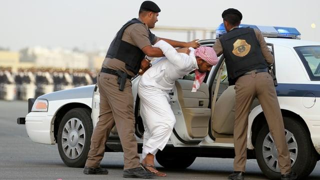 Polizisten halten einen Mann fest
