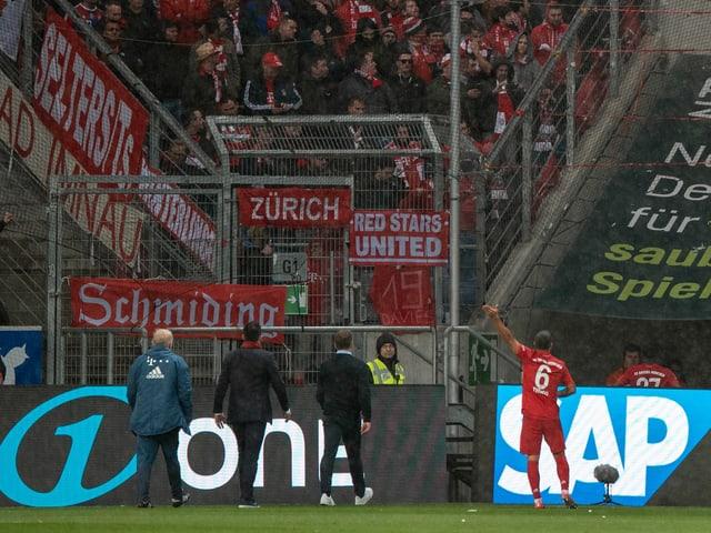 Spieler und Verantwortliche von Bayern München diskutieren mit den Fans in der Kurve.