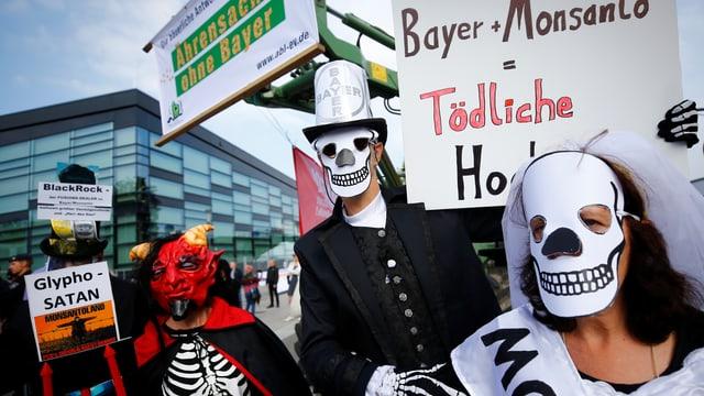 Als Skelette und Teufel verkleidete Protestierende mit Protestschildern.
