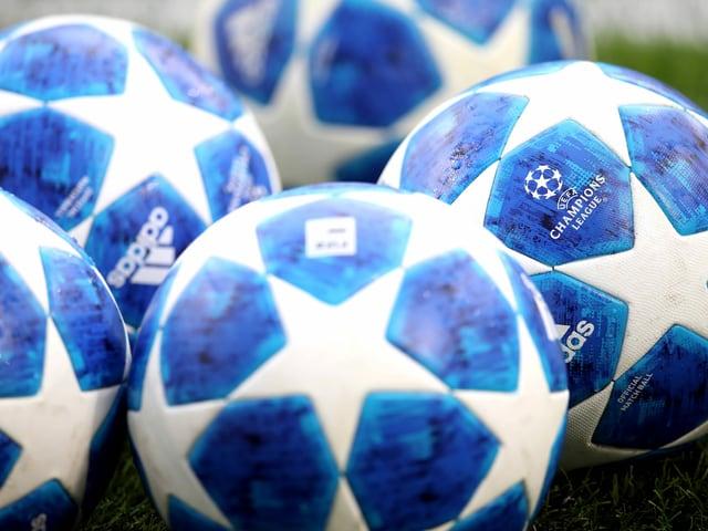 5 Champions-League-Bälle auf dem Rasen.