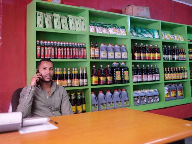 Ein Mann sitzt in einem kleinen Laden.