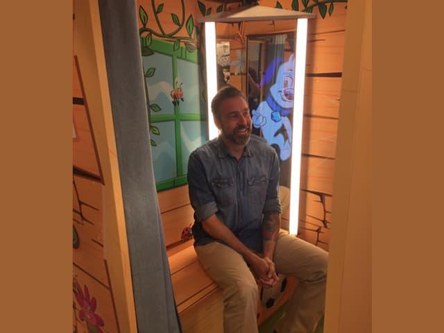 Mann sitzt in Umkleidekabine mit Smartmirror