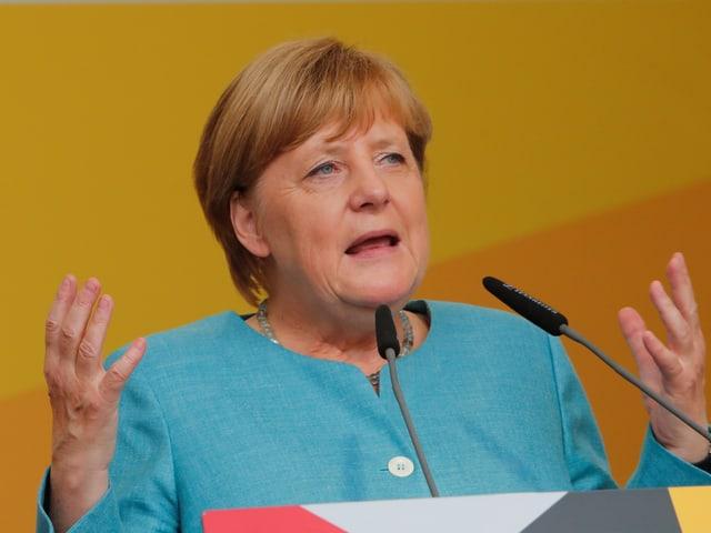 Angela Merkel mit erhobenen Händen an einem Rednerpult