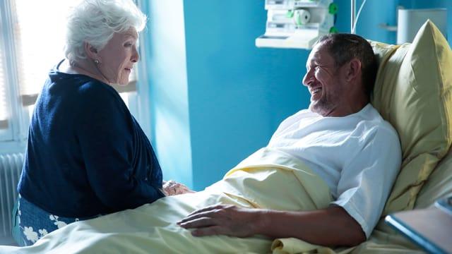Alte Frau sitzt im Spital am Bettrand, im Bett ein Mann.