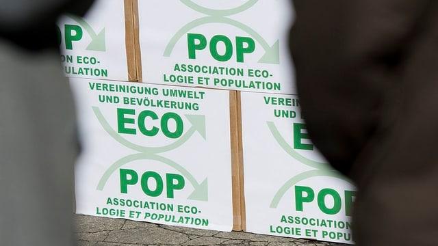 Gestapelte Kartons mit grüner Ecopop-Aufschrift.