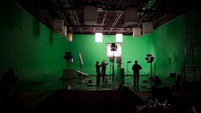 Ein Studio mit Lampen und Greenscreen. In der Mitte stehen drei Menschen.
