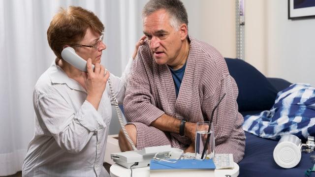 Symbolbild: Eine Frau mit Telefon am Ohr, Neben ihr ein Mann im Bademantel