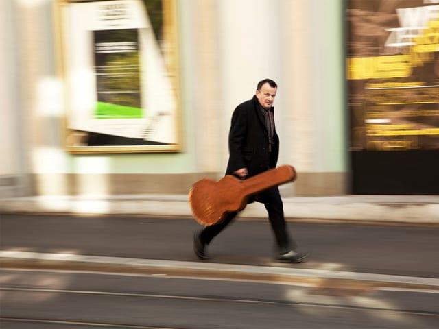 Philipp Fankhauser mit Gitarrenkoffen auf dem Weg zu einem unbekannten Ziel auf einem Bild, das viel Bewegung zeigt.