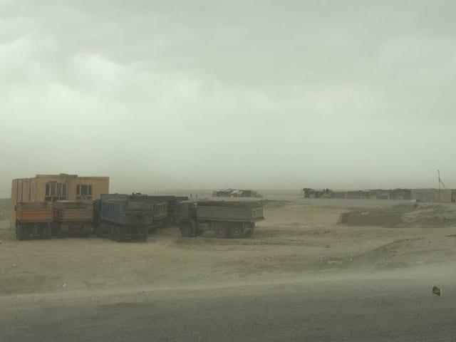 Herumstehende Lastwagen in einer Wüstenlandschaft in Grenznähe.