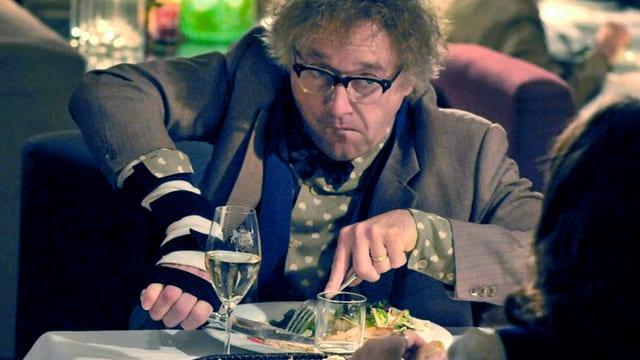 Ein Mann mit krausen Haaren und Brille sitzt an einem Tisch und hantiert mit Gabel und Messer.