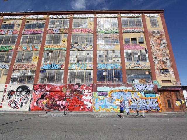 Bunt besprayte Fassade eines Fabrikgebäudes