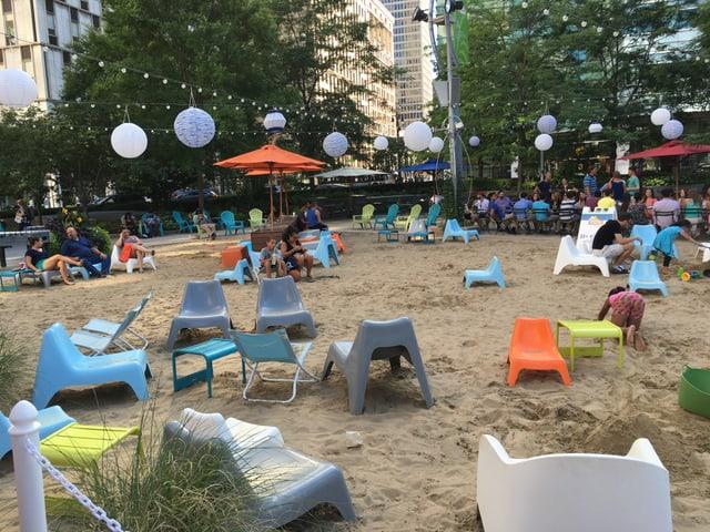 Farbige Plastikstühle auf einem Sandstrand mitten in der Detroiter Innenstadt.