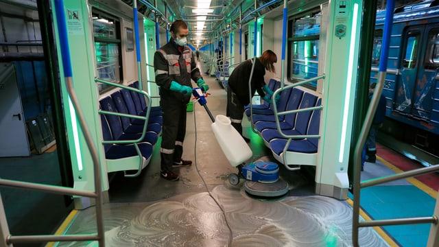 Menschen putzen U-Bahn.
