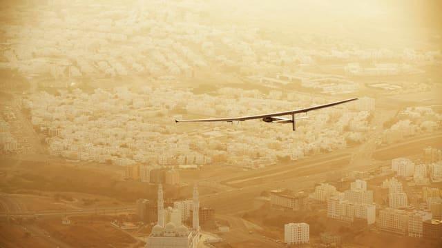 Eroplan solar sin in sgol sur l'Oman, da vesair sut l'eroplan ina moschea e pliras chasas alvas.
