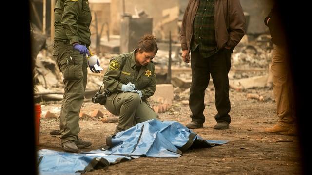 Polizistin kniet vor einem abgedeckten Körper