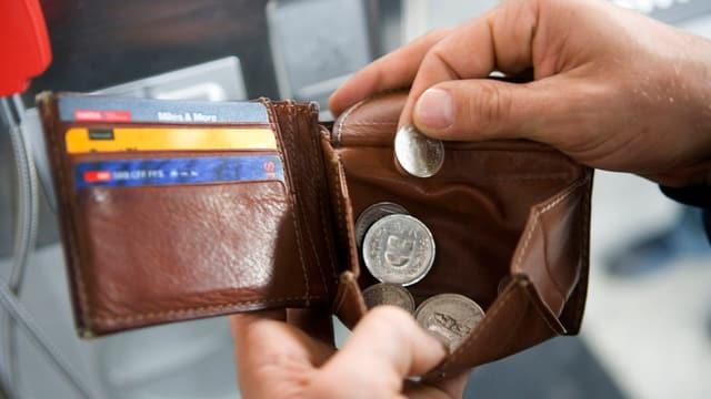 Braunes Portemonnaie mit offenem Münzfach, darin ein paar Schweizer Franken.