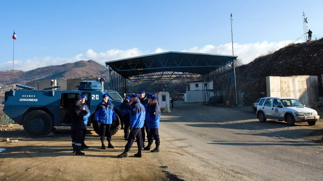 EULEX-Polizisten stehen vor einem Grenzübergang im Kosovo.
