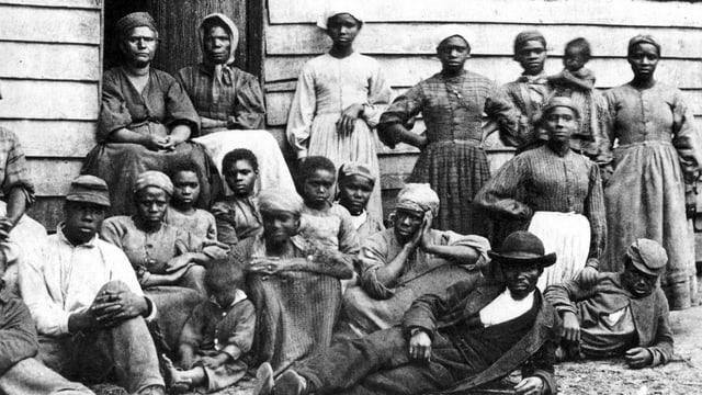 Schwarze Sklaven posieren vor einer ärmlichen Hütte.