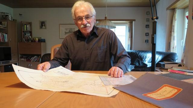 Älterer Mann sitzt vor einer historischen Karte.