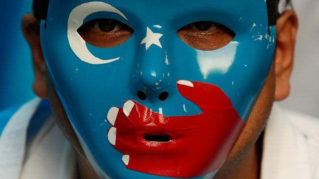 Uigurischer Aktivist mit einer Maske