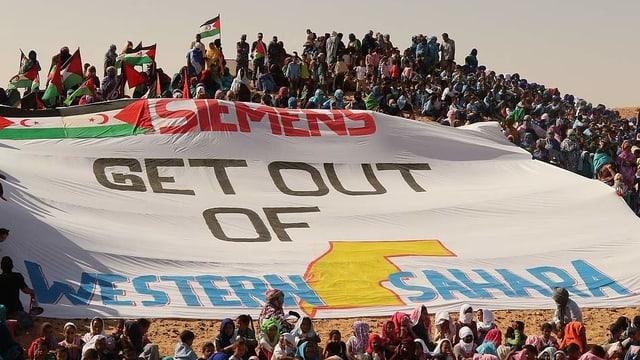 """Protestierende und Transparent mit der Aufschrift """"Siemens get out of Western Sahara"""""""