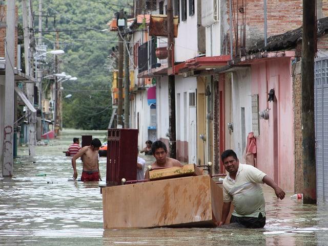 In einer überluteten Strasse packen Mexikaner Kisten