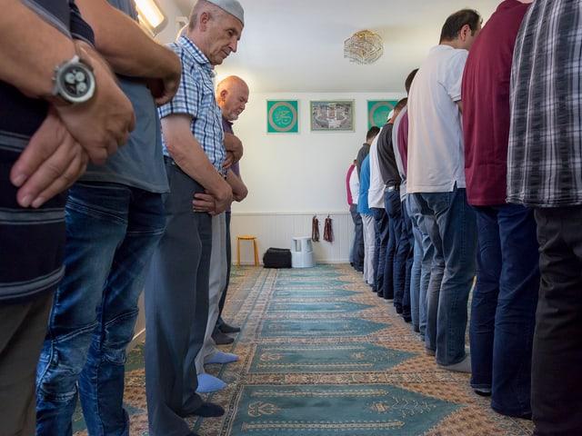 Männer stehen mit den Händen verschränkt im Gebetsraum der Moschee.