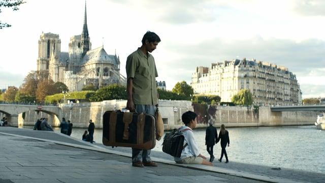 Ein Vater mit sienem Sohn befinden sich mit Koffer an der Seine in Paris.