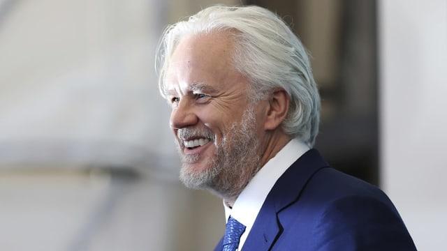 Ein Man mit grauen Haaren und grauem Bart lächelt dem Publikum zu.
