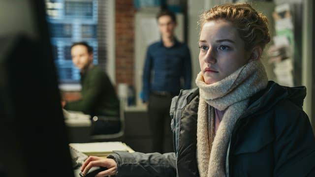 Eine Frau sitzt an einem Bürotisch, im Hintergrund schauen ihr zwei Männer zu