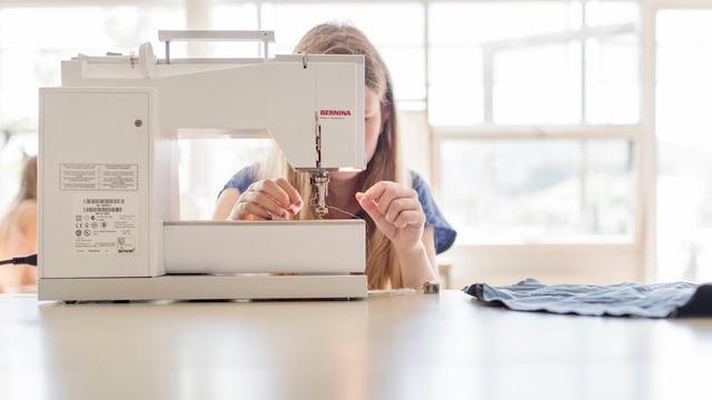 Ein Mädchen fädelt einen Faden in eine Nähmaschine ein