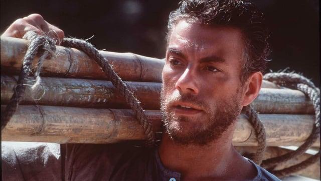 Jean Claude Van Damme mit Holz auf der Schulter.
