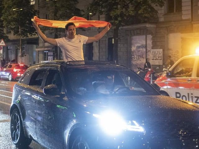 Mann mit Schweizerflagge im Auto.