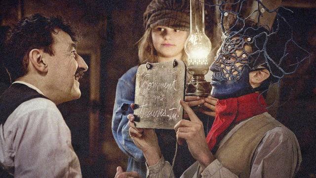 Ein Mann mit Maske zeigt einem anderen Mann ein Schild. Im Hintergrund ein Mädchen.