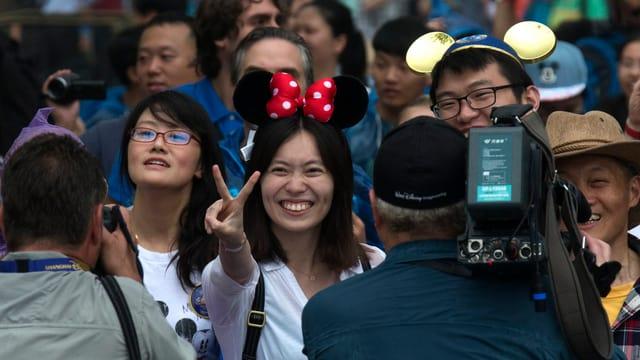 Chinesin mit Minnie-Mouse Ohren macht ein Peace-Zeichen