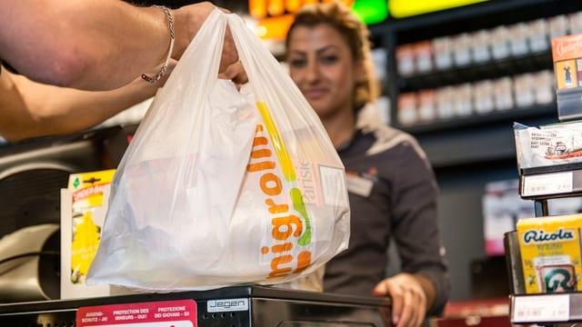 Hand einer Kundin in einem Tankstellenshop nimmt einen Plastiksack von der Kassentheke